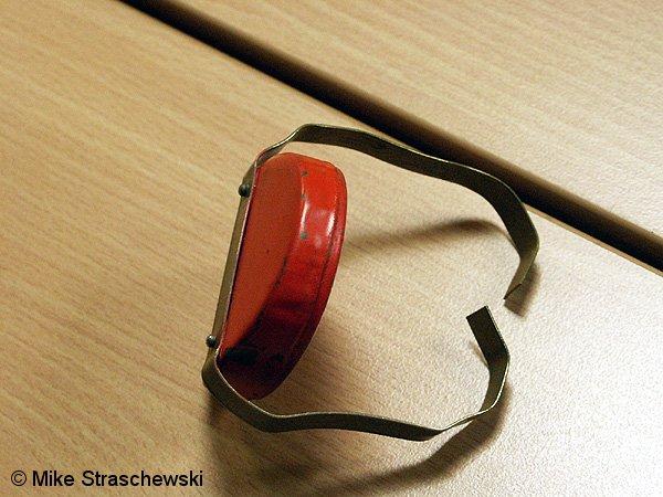 Eine Knallkapsel: im roten Behältnis befindet sich der Sprengstoff, mit den Bügeln wird die Knallkapsel am Schienenkopf fixiert.